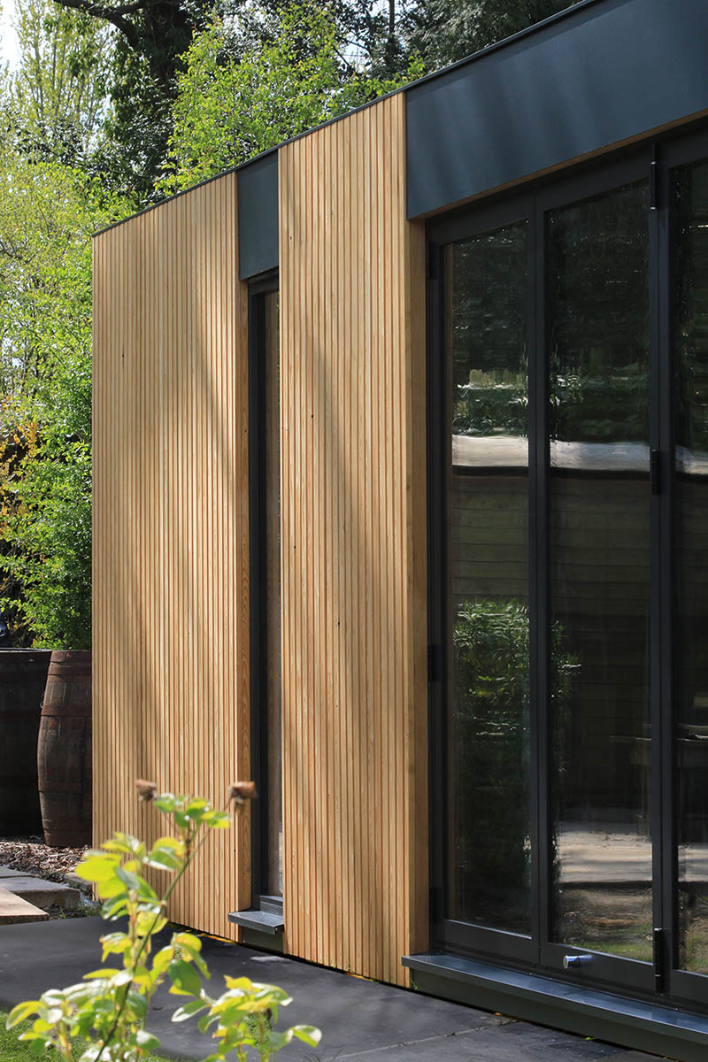 Genus garden room anthracite doors and with larch cladding